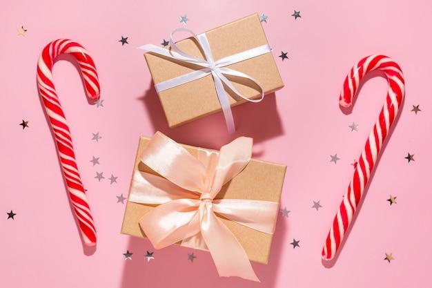 Presentes com doces de natal vermelhos e estrelas de confetes derramam sobre um fundo rosa pastel, vista superior. postura plana. ano novo de férias, conceito de atmosfera de celebração