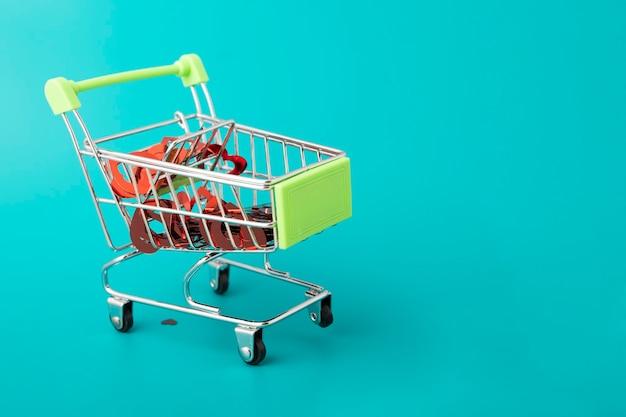 Presentes de amor no dia dos namorados, muitos corações em um carrinho de compras do supermercado em um fundo verde com espaço de cópia