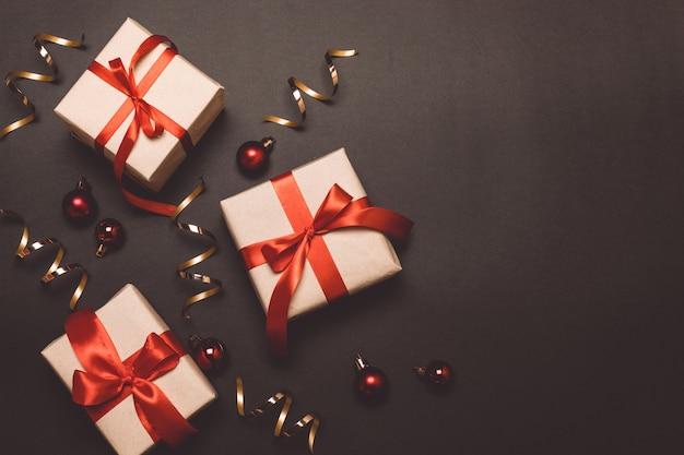 Presentes de artesanato de natal com fitas vermelhas e confetes de ouro sobre um fundo de contraste escuro