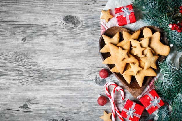 Presentes de biscoitos e galhos de árvore do abeto em uma mesa de madeira.