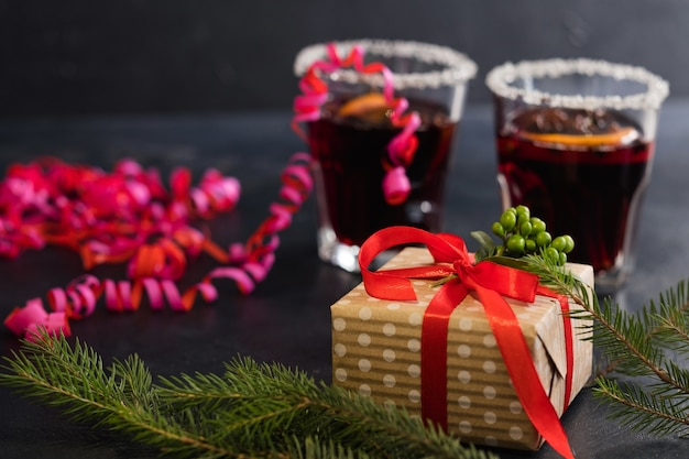Presentes de feriado e conceito de celebração de natal. presente embrulhado em papel artesanal amarrado com fita vermelha na parede escura. decoração da temporada festiva de galhos de árvores de abeto com vinho quente e serpentina.