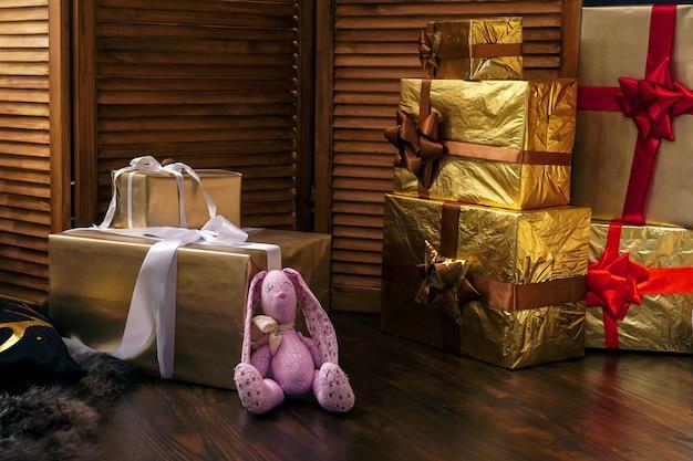 Presentes de natal com fitas vermelhas e papel dourado. presentes de brinquedos