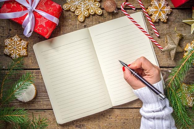 Presentes de natal com galhos de árvores e biscoitos de gengibre ao lado de um caderno vazio