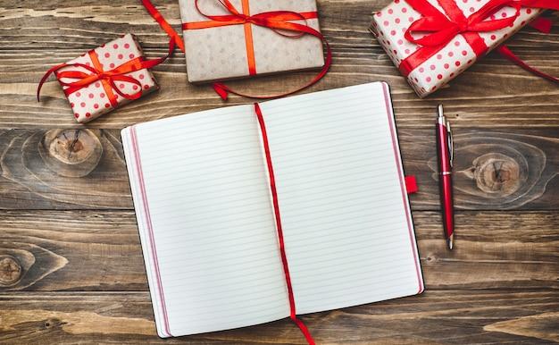 Presentes de natal com uma decoração em uma placa de madeira e um caderno com uma caneta para registros