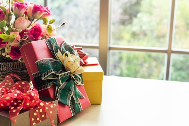 Presentes de natal com vaso rosa e chapéu de papai noel no interior da mesa de madeira da sala vista através da janela com árvore