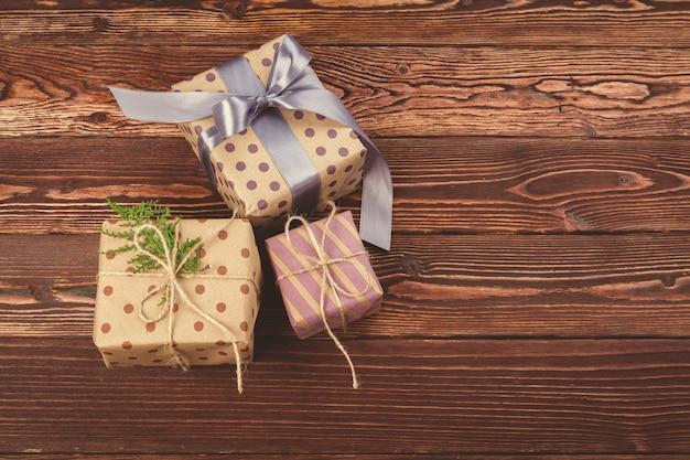 Presentes de natal decorados elegantes sobre fundo de madeira marrom