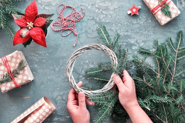 Presentes de natal diy e decorações feitas à mão, caixas de presente embrulhadas em papel de embrulho artesanal. mãos fazendo guirlanda de natal.