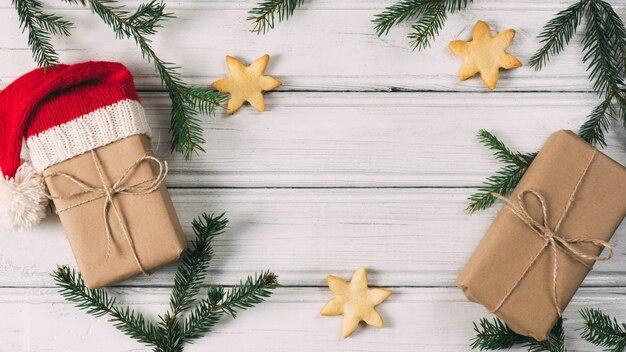 Presentes de natal e ano novo em cima da mesa com galhos de árvores de natal e biscoitos com doces