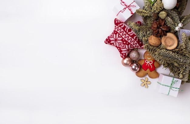 Presentes de natal e coisas bonitas são dispostas em um círculo sobre um fundo branco.