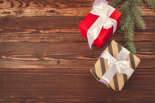 Presentes de natal e galhos de pinheiro na mesa de madeira, vista superior