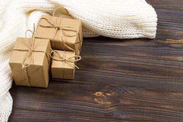 Presentes de natal e lenço branco em uma mesa de madeira preta