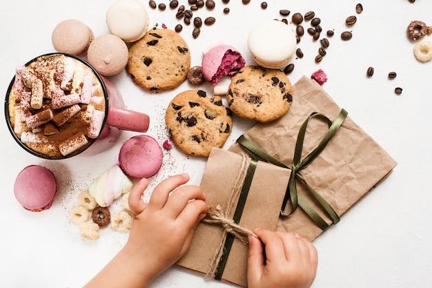 Presentes de natal e surpresas de crianças. criança preparando pequenos presentes para os pais com cacau e macarons coloridos, zéfiros e bolinhos de chocolate nas proximidades. imagem de vista superior