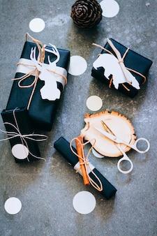 Presentes de natal em embalagem preta com etiquetas, confetes e decoração em madeira sobre um fundo cinza