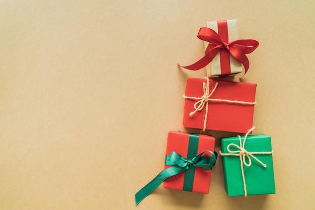 Presentes de natal em fundo de papel com decoração, bagas, estrelas, flocos de neve e copyspace. vista plana, vista superior