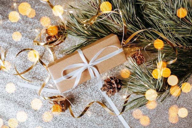 Presentes de natal em luzes com pinhas e ramos de abeto em um ambiente festivo de ano novo em um fundo prateado