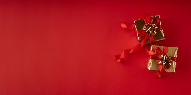 Presentes de natal em papel dourado com uma fita vermelha