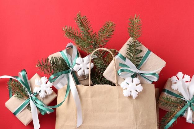 Presentes de natal em papel kraft com fitas verdes e brancas em saco de papel.
