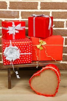 Presentes de natal em um banquinho em uma parede de tijolos marrons