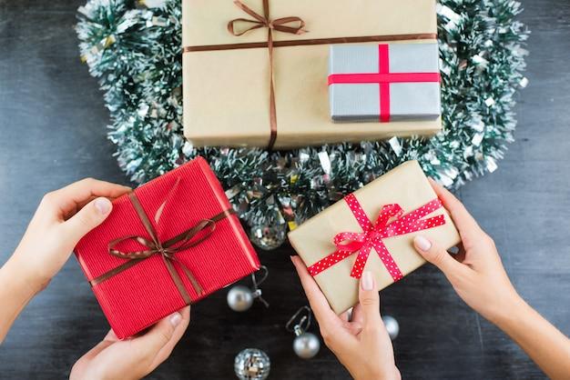 Presentes de natal em uma mesa com preto e mãos segurando presentes