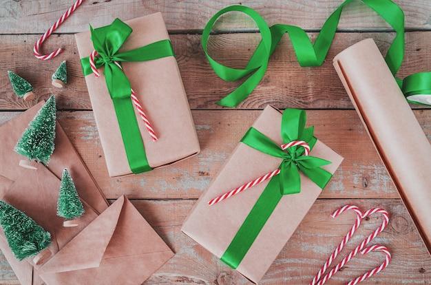 Presentes de natal embrulhado em papel ofício com fita verde vista superior plana leigos na madeira