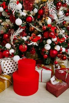 Presentes de natal embrulhado em papel vermelho clássico, fundo com bokeh de luzes de natal turva debaixo da árvore de natal