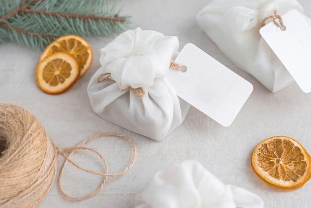 Presentes de natal embrulhados em tecido branco furoshiki, etiquetas e fatias de laranja secas. presente amigável de eco.
