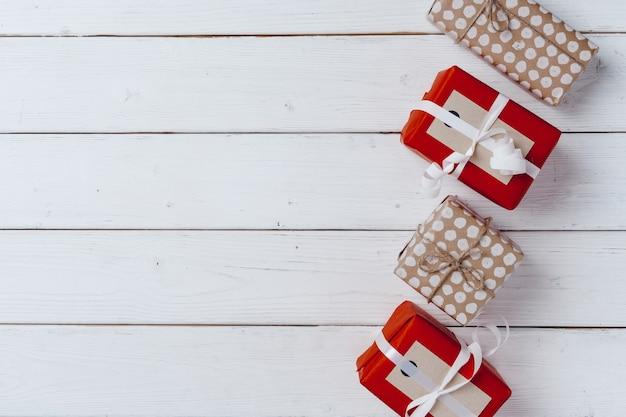 Presentes de natal embrulhados em uma placa de madeira branca, copie o espaço