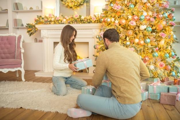 Presentes de natal. jovem casal feliz sentado perto da árvore de natal e trocando os presentes