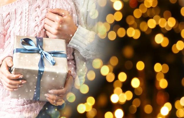 Presentes de natal nas mãos de um homem e de uma mulher. feriado. foco seletivo.