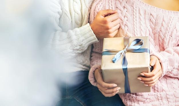 Presentes de natal nas mãos de um homem e uma mulher, foco seletivo.