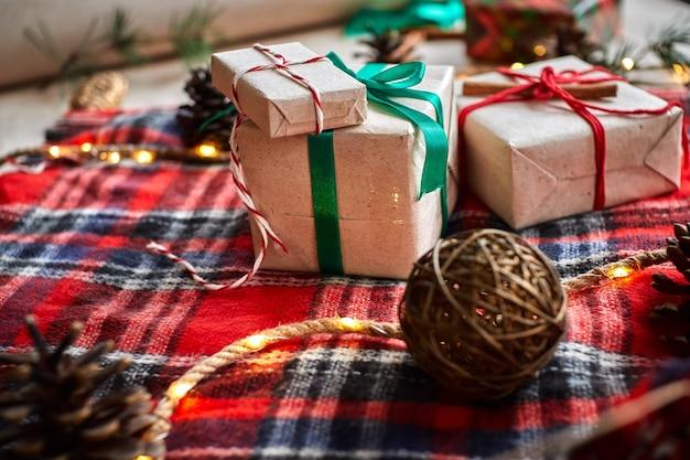 Presentes de natal no fundo de uma manta xadrez de lã vermelha com guirlandas de cones e ramos de abeto