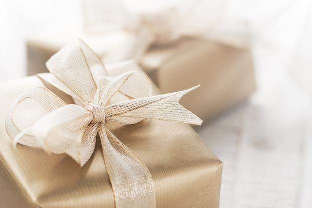 Presentes de natal ou presentes com elegantes decorações de arco e natal no fundo nevado brilhante, conceito de natal