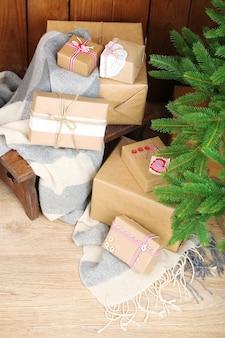 Presentes de natal perto da árvore de natal em uma superfície de madeira