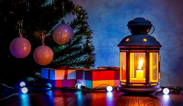 Presentes de natal sob a árvore de natal à luz de uma lanterna com uma vela