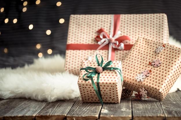 Presentes de natal sobre luzes em fundo escuro. fitas coloridas. decorações de férias felizes.