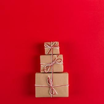Presentes de papel ofício e cordas em forma de árvore de natal em um vermelho, natal, copyspace cartão.