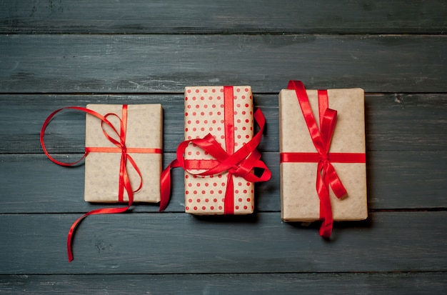 Presentes diferentes com fita vermelha em fundo de madeira