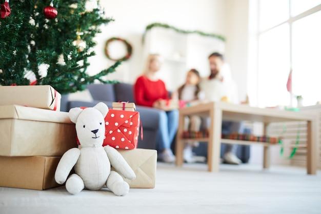 Presentes do papai noel, ursinho de pelúcia, família desfocada