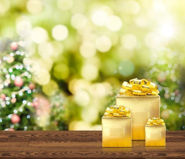 Presentes dourados na mesa de madeira com árvore de natal borrada luz bokeh