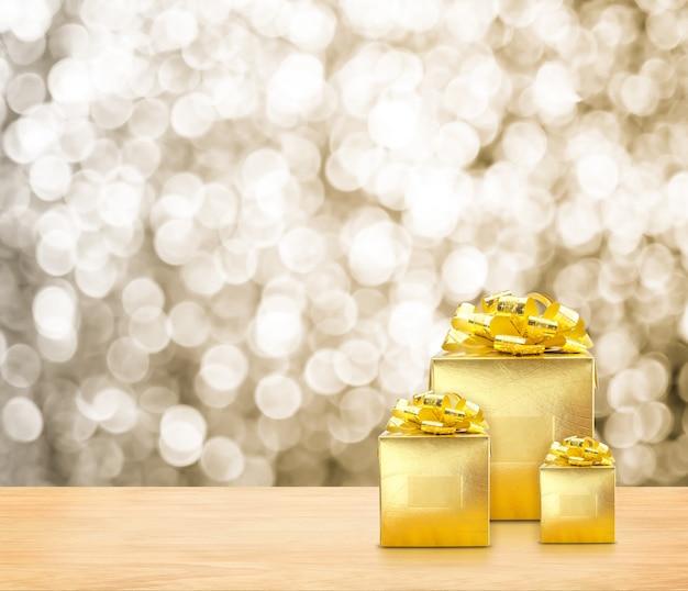 Presentes dourados no tampo da mesa de madeira com luz sparkling do bokeh do ouro.