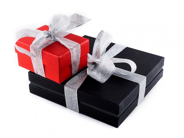 Presentes em caixas pretas e vermelhas são amarrados com uma fita de prata.