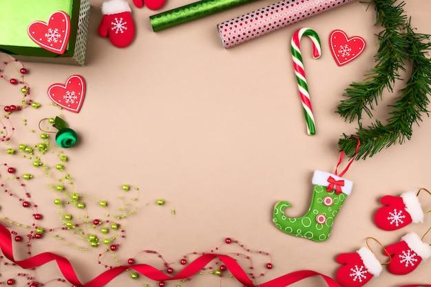 Presentes em embalagens brilhantes, localizadas em um fundo bege, em que são rolos de papel brilhante, pequenas luvas, galhos de pinheiro, miçangas, uma bota, fita encaracolada, brinquedo de natal.