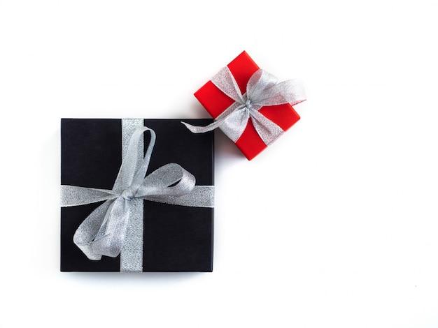 Presentes em pacotes pretos e vermelhos são amarrados com uma fita de prata.