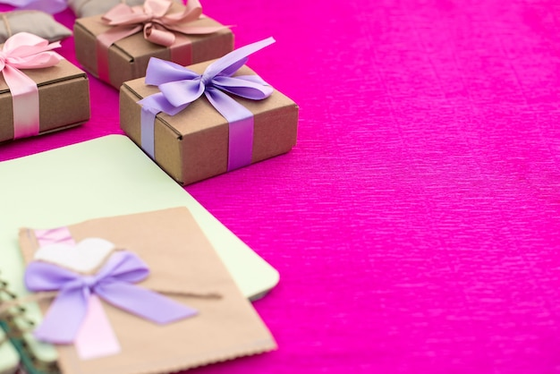 Presentes embalados em caixas kraft amarradas com fita de cetim.