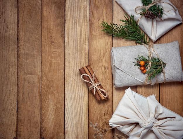 Presentes embrulhados em tecido com decoração vegetal sobre madeira