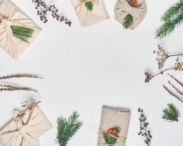 Presentes embrulhados em tecido com decoração vegetal
