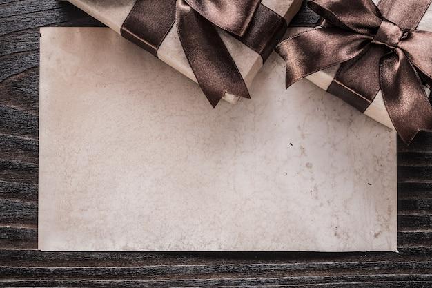 Presentes encaixotados com papel amarrado fitas marrons na placa de madeira