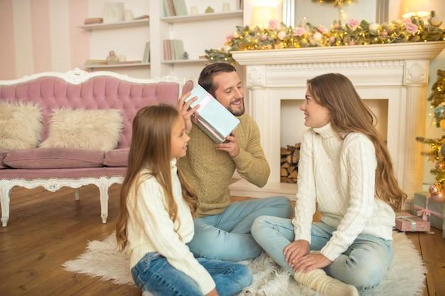 Presentes. família jovem sentada no chão e animada com os presentes de natal