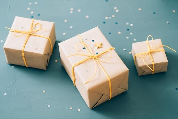 Presentes feitos à mão. três caixas de presente embaladas em papel artesanal e amarradas com barbante amarelo na parede azul.