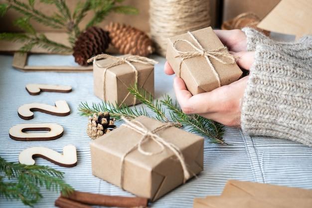 Presentes feitos de papel kraft, galhos de árvores de natal, números de madeira 2021, cones, atmosfera festiva, close-up. preparação para o ano novo, embrulho de presente, materiais naturais.